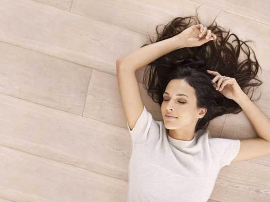 Suelo radiante en el que se ha tumbado una mujer joven morena con el pelo largo.