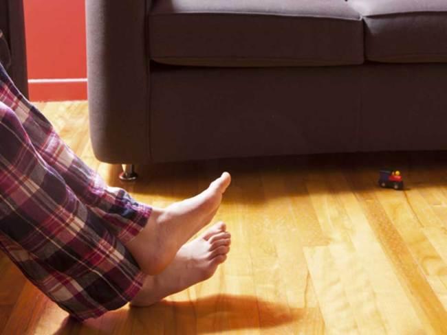 Suelo radiante en una casa donde aparecen los pies descalzos de un chico sentado en un sofá.