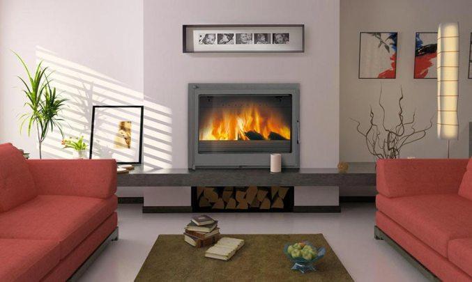 Chimenea en casa donde aparece una chimenea en un salón de casa. Con dos sofás rojos y una mesa de centro.