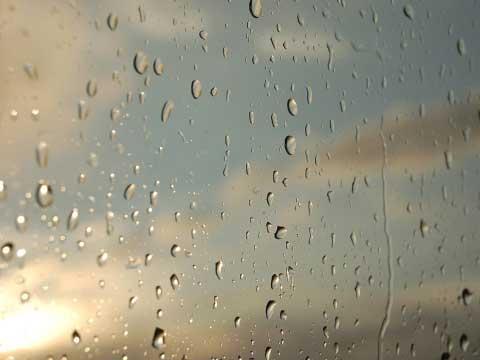 Humedades exterior de casa donde aparece una ventana con pequeñas gotas de lluvia.