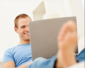 Happy young boy working on a laptop while relaxing at home