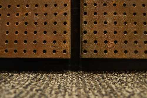 Two modernized elevator interiors incorporate wall panels that have been treated to look worn and weathered to match the design scheme of the building.
