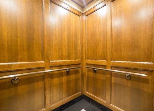 Classic finishes within Minnesota State Capitol Govornor's elevator include rich veneer, extruded Oxidized Bronze Handrails with Custom Stand-offs, coffer ceilings