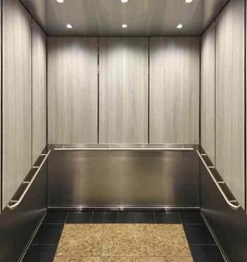 A photo of the elevator at Marriott Residence Inn with laminate upper panels in solar oak and lower panels in 5WL patterned stainless steel.