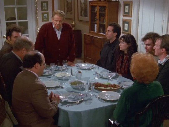 Frank Costanza (Jerry Stiller), standing, begins the celebration of Festivus. The exploits of force are upon us.