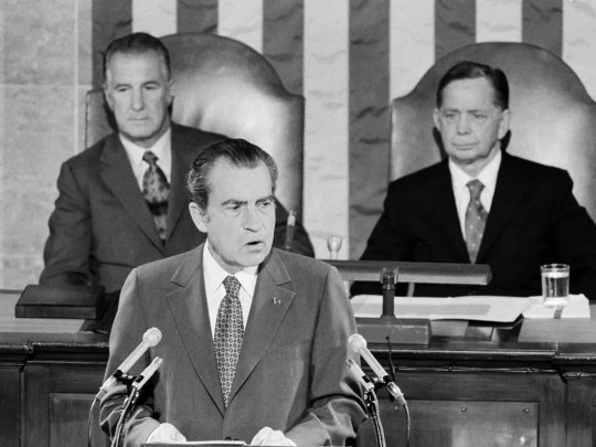 President Richard Nixon addresses a joint session of Congress on his return to Washington from a four-nation, 13-day summit trip, June 2, 1972. In background are Vice President Spiro T. Agnew, left, and House Speaker Carl Albert.