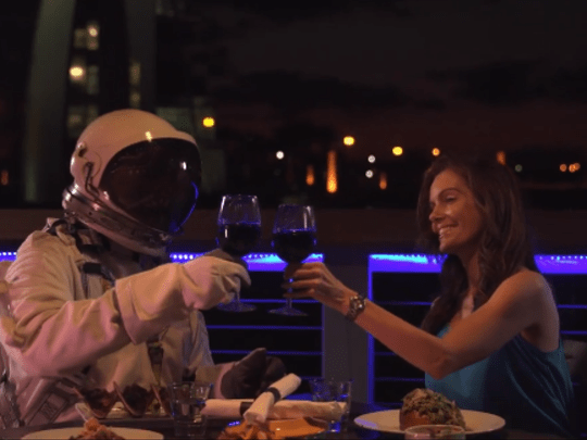 This still photo from a video shows Starman and a date having a romantic dinner at the Cove area of Port Canaveral, with the port's Exploration Tower in the background..