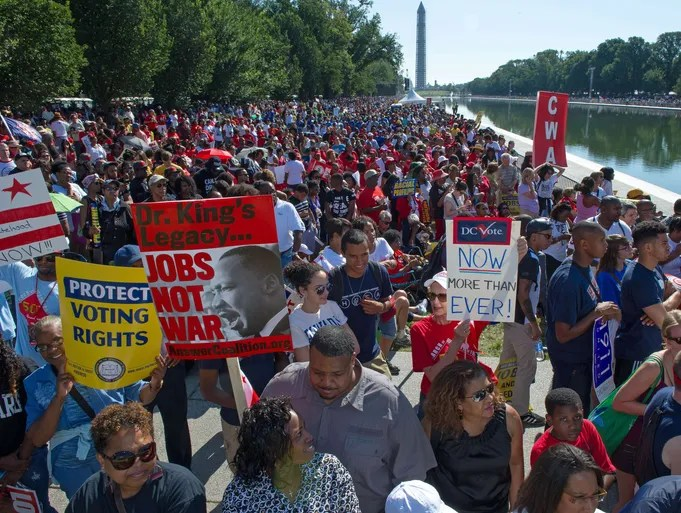 """Thousands of people line the reflecting pool near the Lincoln Memorial while listening to speakers at the 50th anniversary of the March on Washington and Dr. Martin Luther King, Jr.'s """"I have a Dream"""" speech  in Washington, DC."""
