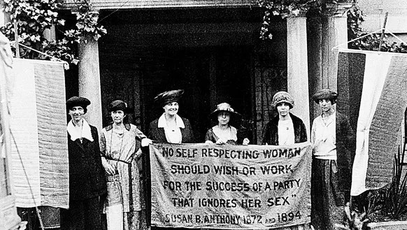 Suffragettes march with the green, white and purple