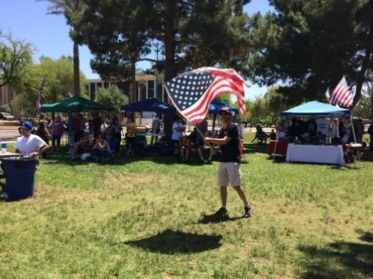 Russell Jaffe waves a flag at a rally outside the Arizona