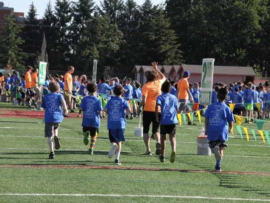 Fourth grade boys run out to the warm up area at Awesome