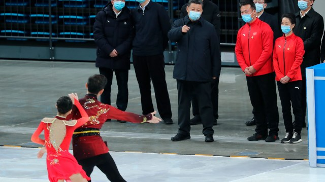 """FILE - In this Jan. 18, 2021, file photo released by China's Xinhua News Agency, Chinese President Xi Jinping, center, watches skaters perform during a tour of venues and preparations for the 2022 Beijing Winter Olympics at the Capital Gymnasium in Beijing. The 2022 Beijing Winter Olympics will open a year from now. Most of the venues have been completed as the Chinese capital becomes the first city to hold both the Winter and Summer Olympics. Beijing held the 2008 Summer Olympics. But these Olympics are presenting some major problems. They are already scarred by accusations of rights abuses including """"genocide""""against more than 1 million Uighurs and other Muslim ethnic groups in western China. (Yao Dawei/Xinhua via AP, File)"""