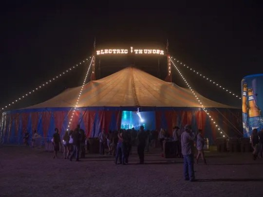 Festival goers walk around the electric thunder tent
