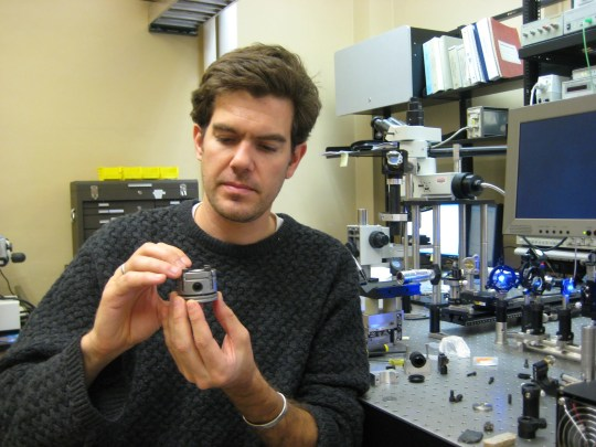Professor Steve Jacobsen of Northwestern University holds a tiny diamond-anvil cell press, inside which a crystal of hydrous ringwoodite is compressed to conditions of 700 km depth.