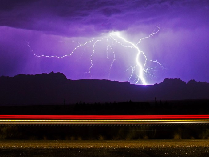 Lightning strikes over Echo Cliffs while lights from