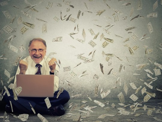 A man sits on a floor, looking at a laptop, as $100 bills fall around him.