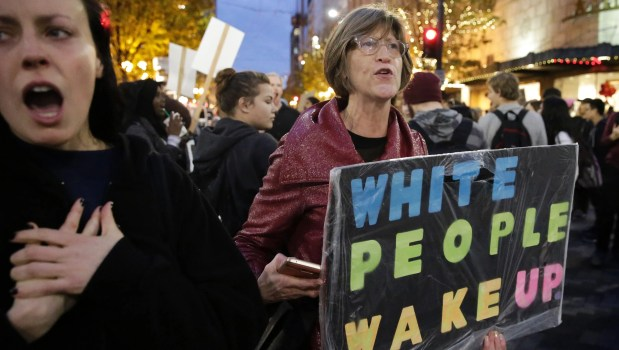 "A woman holds a sign reading ""White People Wake Up"" during a protest against Donald Trump in Seattle on Nov. 14, 2016."