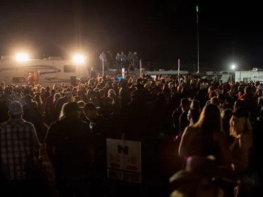 A crowd gathers and dances in the campgrounds at the