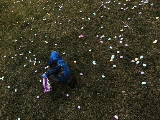 Jacob Medrano, 4, of Flint gathers plastic eggs filled