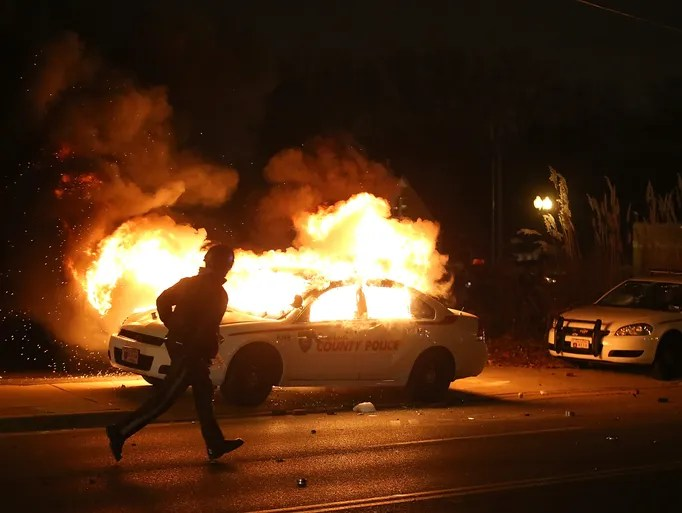 A police officer runs by a burning police car during