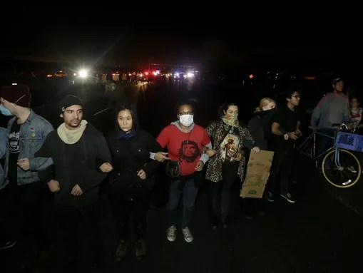 Protesters lock arms as they block traffic on Highway