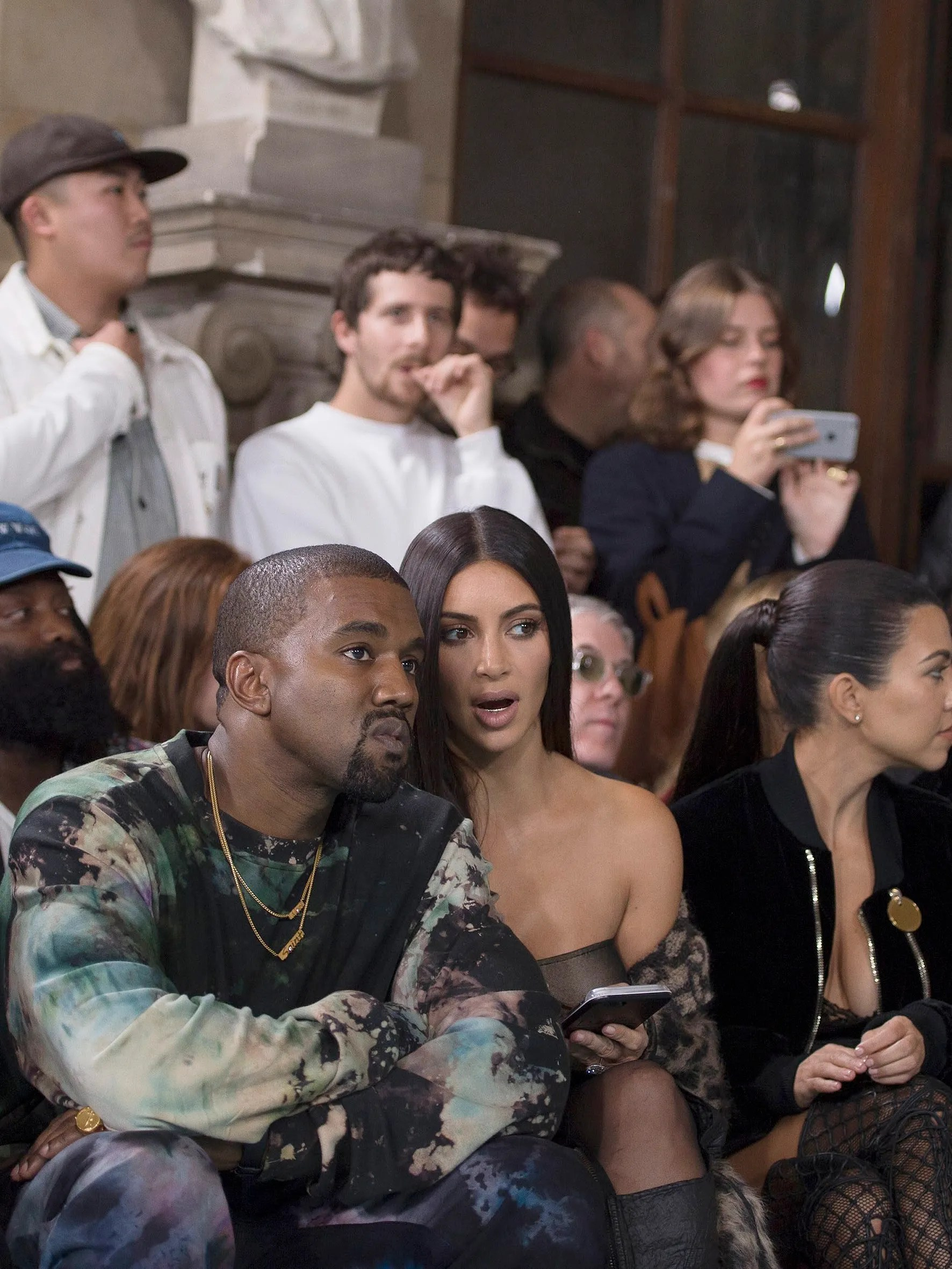 West and Kardashian sit front row at Paris Fashion Week with other members of the Kardashian family.