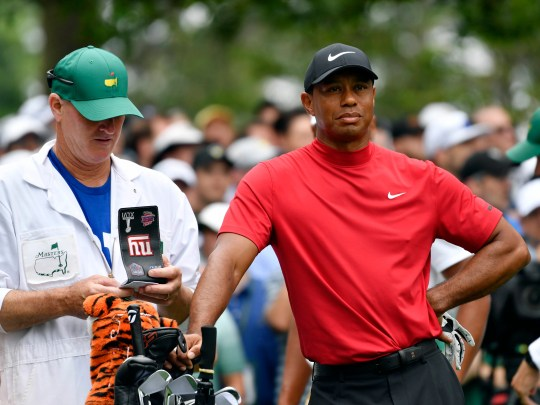Tiger Woods and caddie Joe Lacava on the 4th tee during the final round of The Masters golf tournament at Augusta National Golf Club.