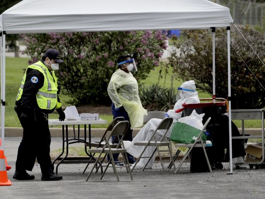 Health workers and security personnel are waiting for patients at a COVID-19 test center on Monday, where the coronavirus epidemic is disproportionately devastating in a predominantly black area of Saint Louis.