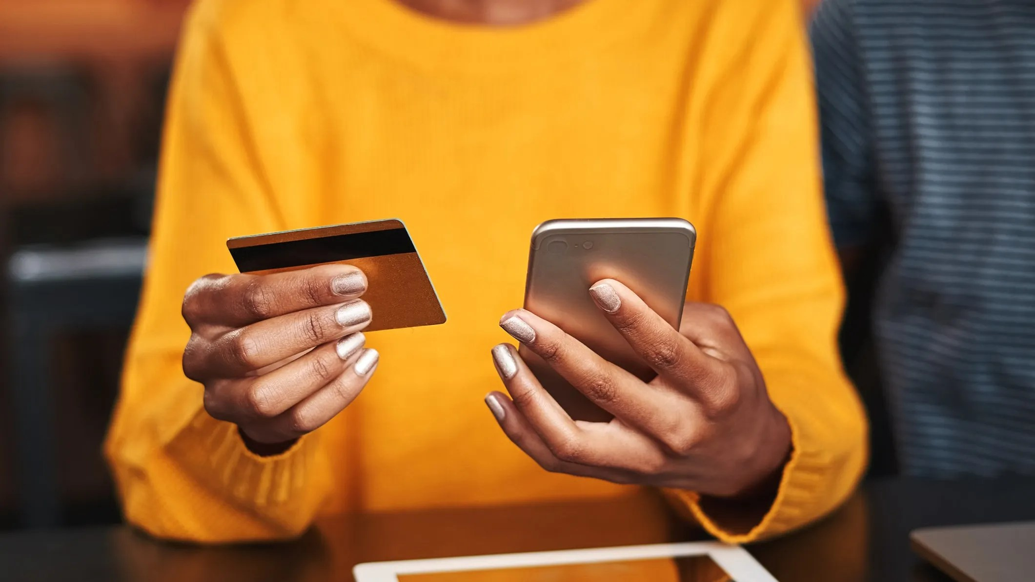 A woman holding a credit card and a mobile phone.