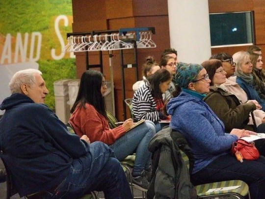 Martin Gugino, left, listens at a talk by West Cosgrove, of Rural & Migrant Ministry in Feb. 2019.