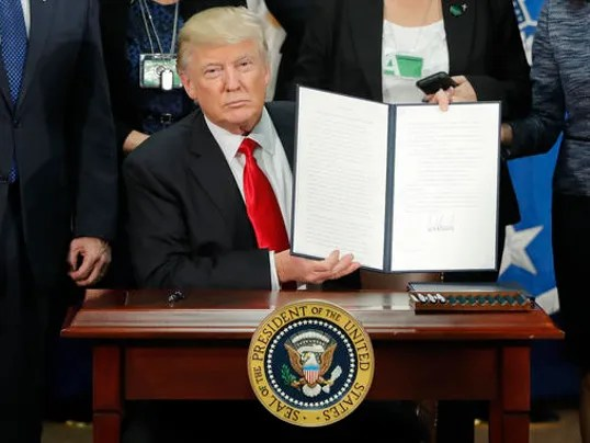 Donald Trump holds up and executive order for border security and immigration enforcement