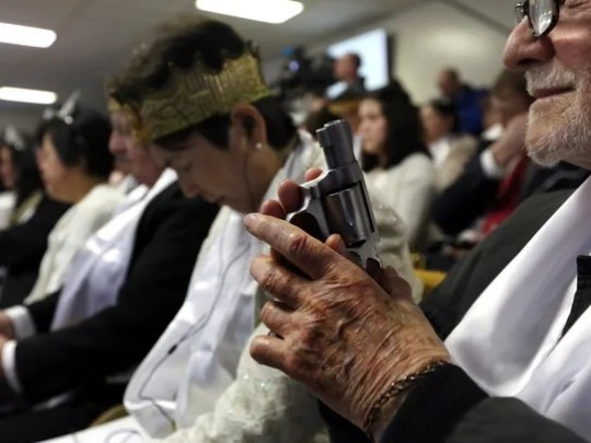 A man holds an unloaded weapon during services at the