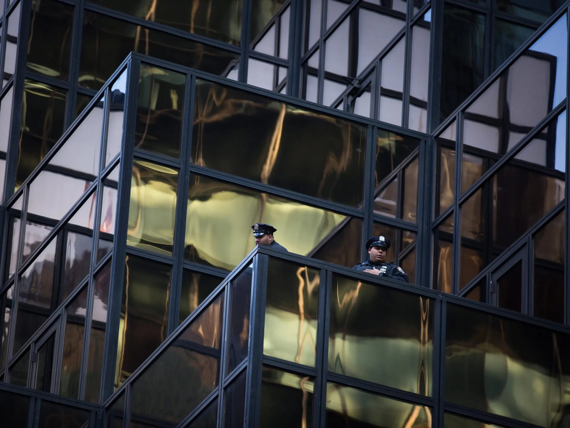 Police officers look down from Trump Tower as thousands