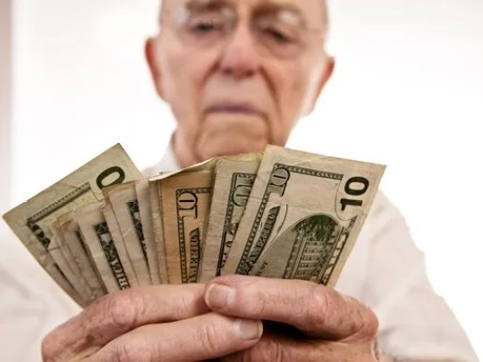 A senior counting a fanned pile of cash.