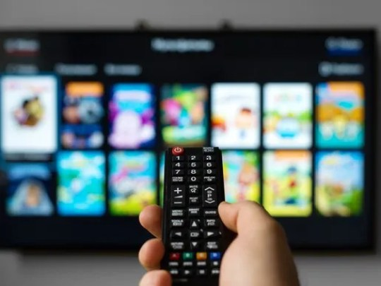 A man pointing a remote at a TV.