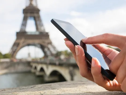 Woman using her Mobile Phone in front of Eiffel Tower