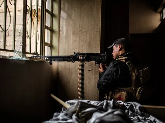 A member of the Iraqi Special Forces fires his machine