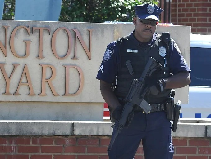 A guard stands outside the gate to the Washington Navy Yard on Sept. 17 in Washington, D.C. Thirteen people, including the gunman, were killed during a shooting at the facility a day earlier.