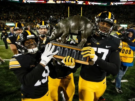 Iowa's Miles Taylor (19) and Iowa's Chauncey Golston (57) carry the Floyd of Rosedale trophy off the field after Iowa defeated Minnesota 17-10 during an NCAA college football game Saturday, Oct. 28, 2017, in Iowa City. (Brian Powers/The Des Moines Register via AP)