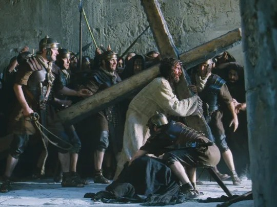 Jim Caviezel, right, portraying Jesus Christ, carries