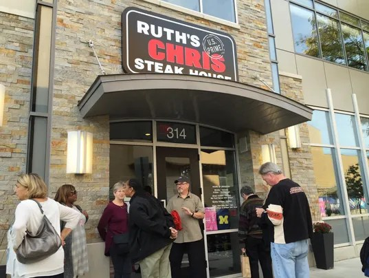 Diners wait outside Ruth's Chris steak house in Ann Arbor to take advantage of Wolverines discount deal based on 78-0 blowout of Rutgers