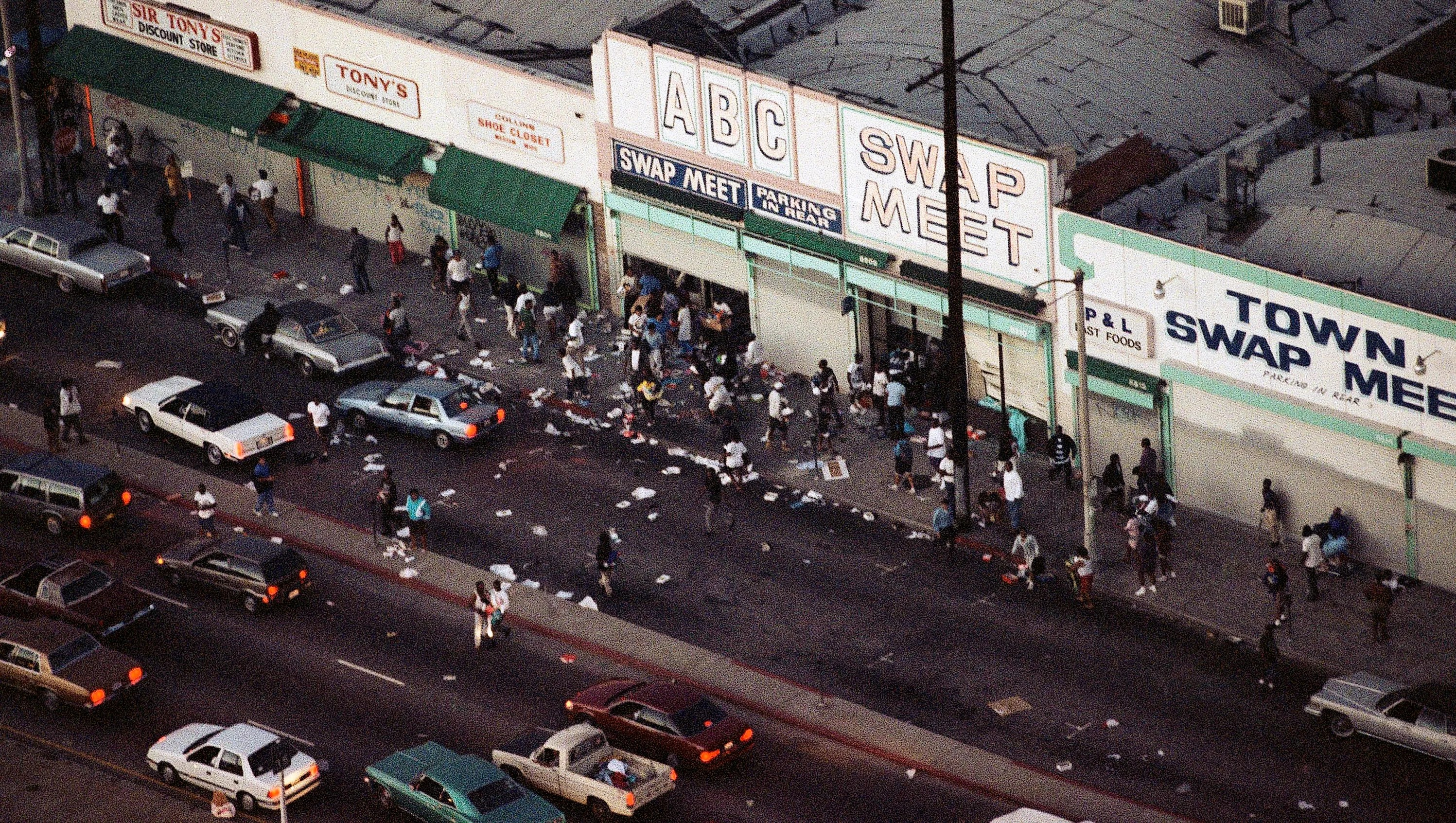 In this April 29, 1992, file photo, people enter and leave a swap meet in Los Angeles. Violence broke out in the area after four Los Angeles police officers were acquitted on all but one charge for the videotaped beating of motorist Rodney King.