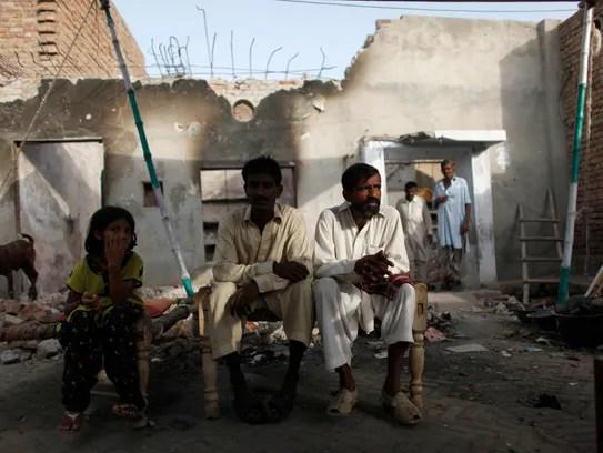 Uma família cristã repousa na frente de seu destruída
