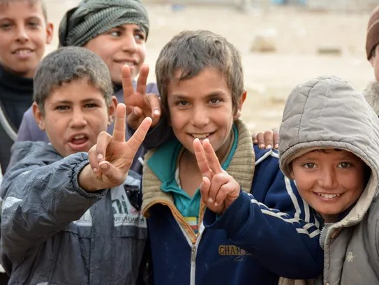 Iraqi children flash the sign of victory in the neighbourhood