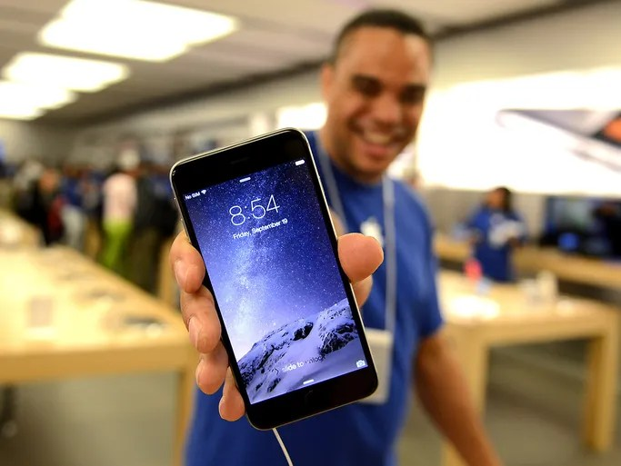 An Apple store employee shows off the new iPhone 6 on Sept. 19 at the Eaton Center in Toronto.