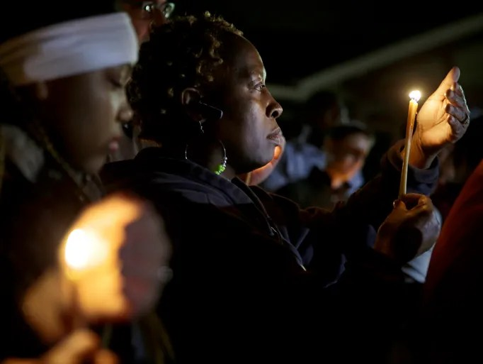 People take part in a candlelight vigil in Ferguson,