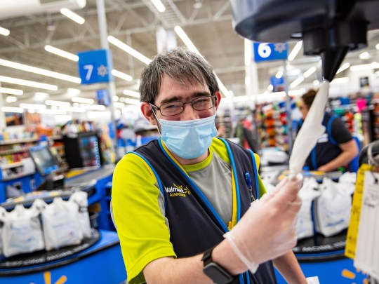 A Walmart employee wearing a mask and plastic gloves.
