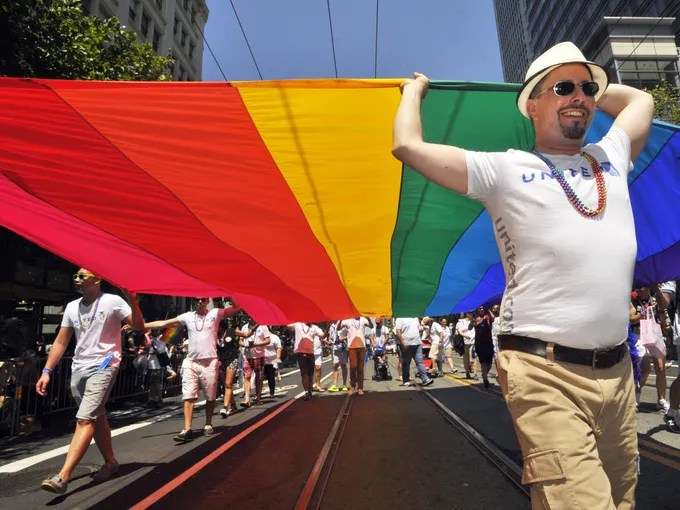 Gay rights supporters carry a rainbow flag along the parade route at San Francisco's gay pride festival.