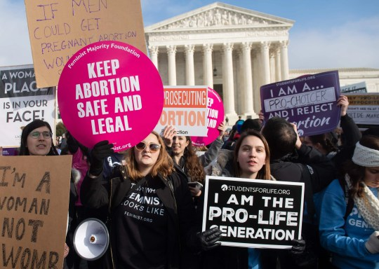 """Pro-choice activists hold signs Jan. 18 alongside anti-abortion activists participating in the """"March for Life"""" in Washington, D.C."""