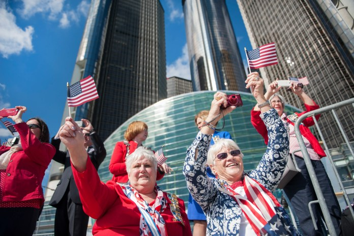 Sharon Hopkins, of Johannesburg, and Liz Soderlund, of the UP, cheer as the USS Detroit arrives at the Riverfront behind the Renaissance Center.